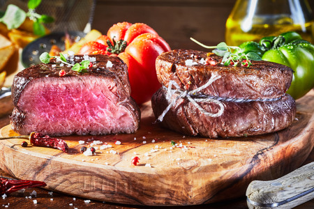 Tender lean medium rare beef fillet steak medallions with one sliced through to show the red meat on a wooden cutting board with tomatoes
