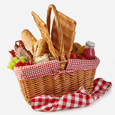 Cesta de picnic de verano llena de comida con fruta fresca y jugo, salami picante, baguettes, tomates y hierbas aisladas en blanco sobre un mantel rústico a cuadros Foto de archivo