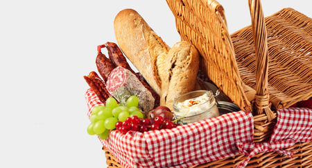Spicy sausages, fresh fruit and baguettes in a wicker picnic basket for a healthy outdoor summer lunch in a close up cropped view on white