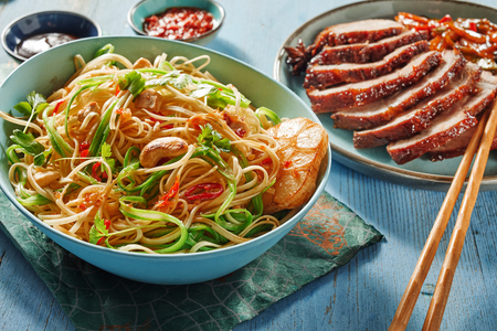Bowl of roasted noodles, garlic and vegetables with barbecued marinated Chinese char siu or pork served for dinner with chopsticks Stock Photo