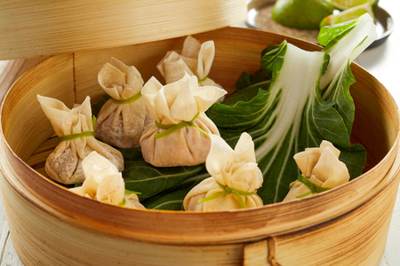 Taditional Asian dim sum dumplings served on green cabbage leaves in bamboo basket