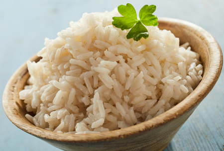 Close up on a bowl of cooked long grain white rice garnished with fresh parsley waiting to be served as a side dish to a meal Stock Photo