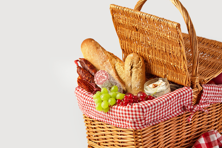 Fresh fruit, bread and cheese in an open wicker picnic basket isolated on white with copy space ready for a summer outdoor lunch