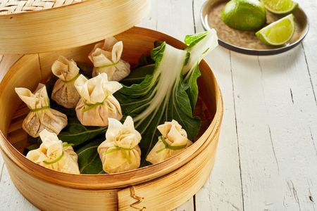 Traditional dim sum dumplings on cabbage leaves in bamboo basket Фото со стока