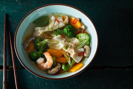 Bowl of wonton dumpling soup wth shrimp and colorful healthy fresh vegetables served in a pottery bowl with chopsticks over a dark background with copy space