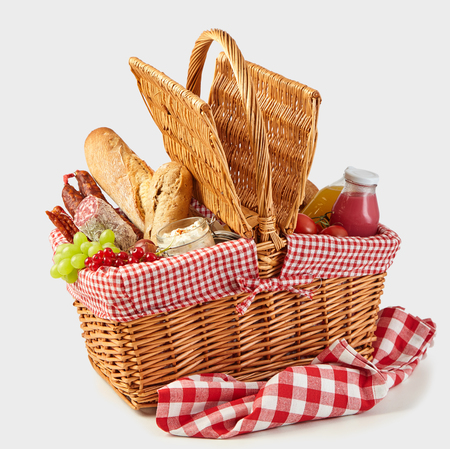 Picnic basket packed with a tasty summer lunch of fresh fruit, juices, tomatoes, spicy sausages and baguettes isolated on white Stock Photo