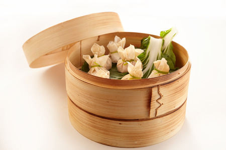 Traditional Chinese dim sum dumplings in bamboo steam cooker Banco de Imagens