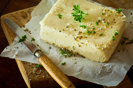 Block of fresh butter with parsley in close up against wooden cutting board