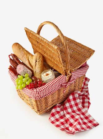 Wicker basket filled with a summer picnic with healthy fresh fruit, bread, cheese and salami sausages high angle isolated on white with checked cloth