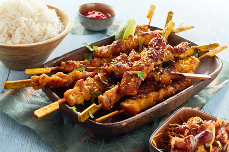 Spicy grilled satay skewers dipped in seasoned soy and peanut sauce served with fluffy white rice