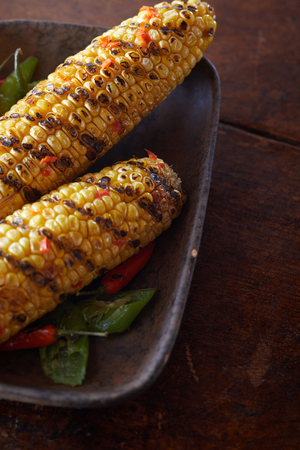 Delicious grilled or barbecued corn on the cob marinated in a spicy chilli marinade and served in a rectangular dish over a dark wood table
