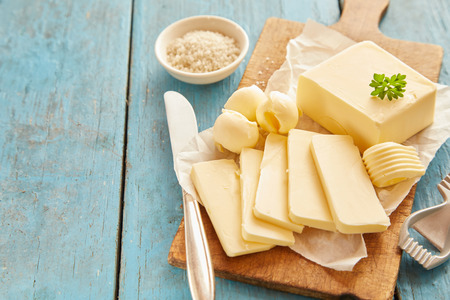 Block of fresh butter sliced on wooden cutting board against blue table Stock Photo