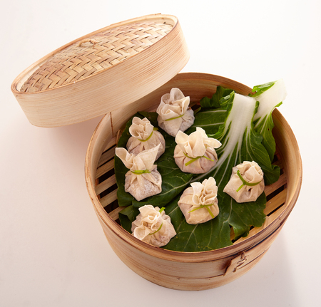 Chinese dumplings in a bamboo steamer on fresh green leaves viewed from above with the lid off to the side over white
