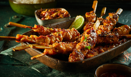 Spicy barbecued satay skewers with diced seasoned meat garnished with fresh herbs and lime and served in a rustic dish over a dark background