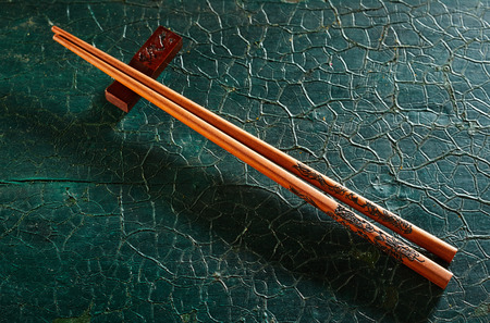 Pair of chopsticks on a rest over weathered textured green wood placed diagonally with copy space viewed from above