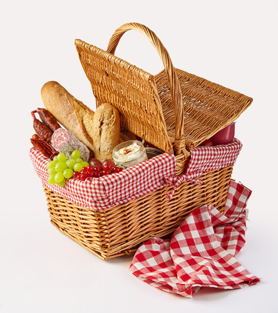 Packed picnic summer lunch in a wicker basket with fresh fruit, cheese, fruit and spicy sausages on a checked red and white cloth over white