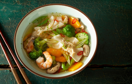 Bowl of Chinese wonton soup with dumplings, fresh vegetables, prawns and chili in a clear broth viewed from above with copyspace