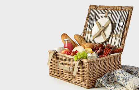 Picnic hamper packed with a tasty summer lunch with fresh fruit and juice, baguettes, spicy sausages and cheese isolated on white with copy space