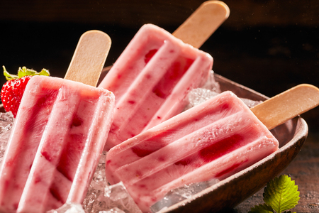 Closeup of three berry ice cream lollies on rustic wooden background Stok Fotoğraf