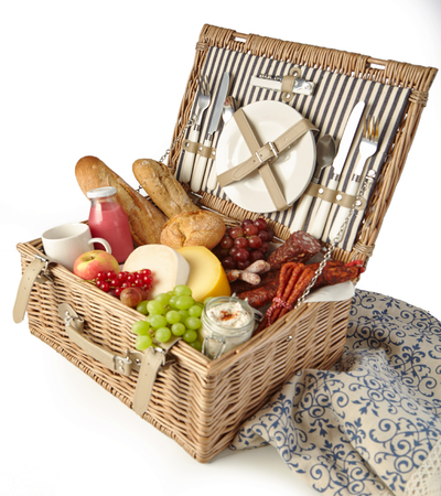 Wicker picnic hamper with assorted fresh food including fruit, juice, spicy sausage, bread and cheese with a tablecloth isolated on white 스톡 콘텐츠