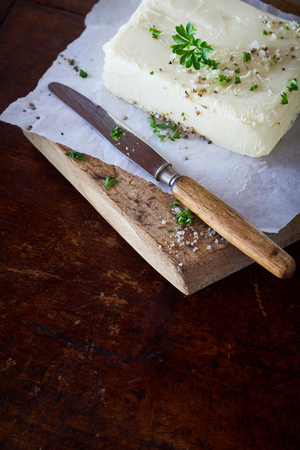 Pat of farm fresh herbed butter on a board seasoned with spices, salt and fresh chopped herbs on a dark background with copy space