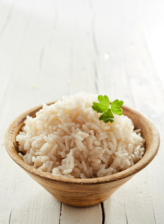 Healthy cooked par-boiled long grained rice in a bowl on a rustic white wooden table with copy space above Banco de Imagens