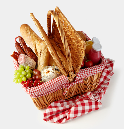 Fresh tasty food in a wicker picnic basket isolated on white with fruit, juice, spicy sausages and crusty bread viewed high angle
