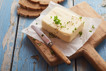 Pat of butter seasoned with fresh herbs, salt and spices on an old wooden board with a vintage knife and rye bread on a rustic table with weathered blue paint Stock Photo