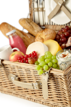 Fresh green grapes and red currants in a picnic hamper with assorted cheeses, spread, baguettes and fruit juice in a close up view