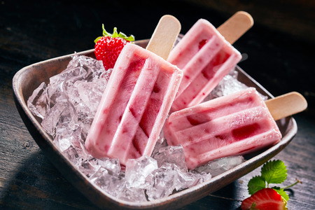 Tasty healthy fresh strawberry or frozen suckers on a bed of ice in a rectangular dish