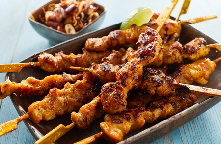 Spicy satay skewers with grilled meat dipped in soy and peanut sauce served in a rustic dish in a close up view