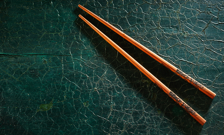 Pair of inscribed wooden chopsticks on a dark green textured background with copy space for placement of food or menu