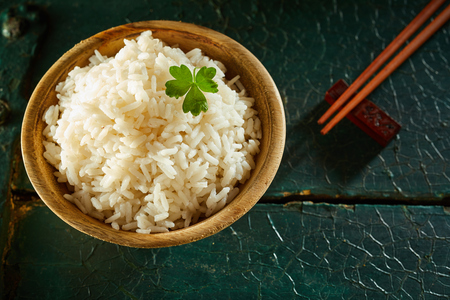 High Angle Close Up Still Life of Small Wooden Bowl of White Rice with Chopsticks and Garnish on Wooden Table with Cracked Painted Surface and Copy Space