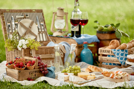 Picnic hamper surrounded by delicious fresh food with berries, fruit, cheese, bread rolls, wraps glasses of red wine, chilled infused water, pastries for dessert and a vintage lantern on green grass Stock Photo
