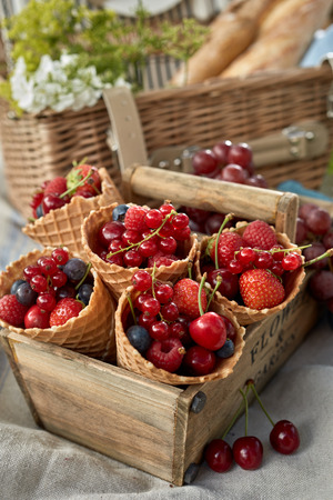 Ice cream cornets filled with assorted fresh berries including raspberries, strawberries, blueberries and cherries in an old wooden crate on a picnic rug Stockfoto