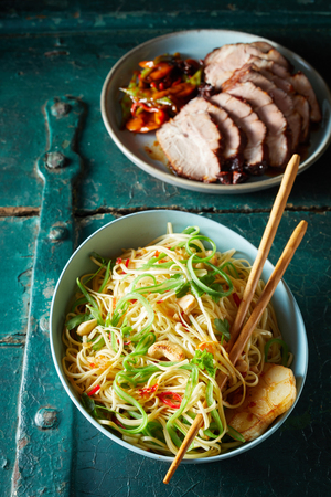 High Angle Close Up View of Vegetarian Chinese Noodle Dish with Cashews and Garlic in Large Blue Bowl with Chopsticks Beside Plate of Roast and Sliced Pork on Cracked Painted Wooden Table Surface