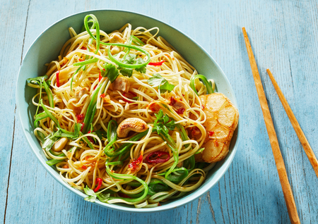 High Angle Close Up Still Life of Spicy Vegetarian Chinese Noodle Dish with Garlic and Cashews in Large Blue Bowl with Chopsticks on Blue Painted Wooden Table Stock Photo