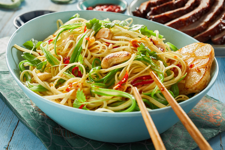 Close Up Still Life of Spicy Vegetarian Chinese Noodle Dish with Garlic and Cashews in Large Blue Bowl with Chopsticks