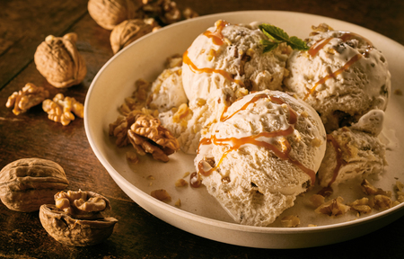 Hoge hoek close-up stilleven van bolletjes esdoorn walnoot ijs besprenkeld met karamelsaus en gegarneerd met walnoten in grote kom op houten tafel
