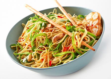 Close Up Still Life of Vegetarian Asian Chinese Noodle Dish with Garlic and Cashews in Large Bowl with Chopsticks on White Background
