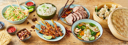 High Angle Panoramic Still Life View of Assortment of Chinese Asian Inspired Food Dishes on Wooden Table Surface