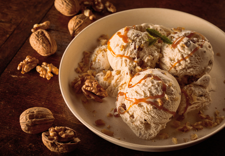 High Angle Close Up Still Life of Scoops of Maple Walnut Ice Cream Drizzled with Caramel Sauce and Garnished with Walnuts in Large Bowl on Wooden Table Zdjęcie Seryjne - 104103030