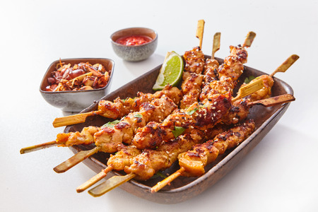 Close Up Still Life of Dish of Grilled Pork or Chicken on Wooden Skewers with Lime Garnish and Sauce on White Studio Background Stockfoto