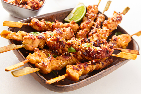 Close Up Still Life of Dish of Grilled Pork or Chicken on Wooden Skewers with Lime Garnish on White Studio Background