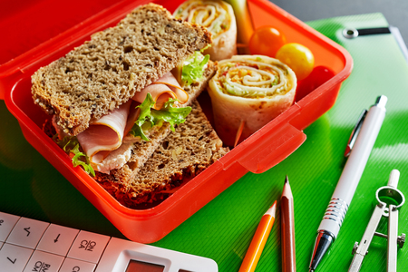 Healthy food in the classroom during a lunch break with an open red plastic box containing a wholegrain ham sandwich, rolled roti roll and diced fresh vegetables on a notebook with pens and calculator