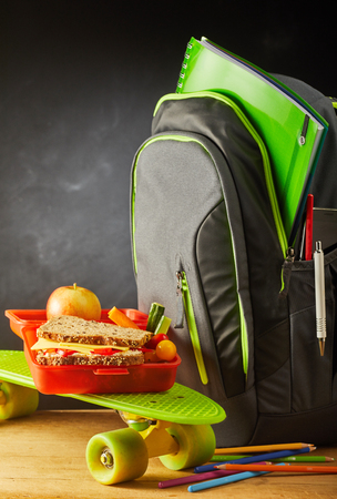 Colorful green roller skate with school bag and open red plastic lunch box with a wholegrain cheese sandwich, vegetables and fresh apple, copy space on slate