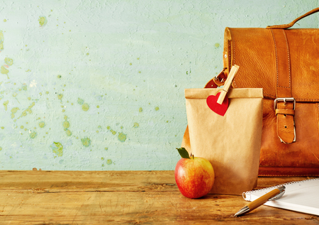 Healthy school lunch concept with brown bag, shiny apple and notebook with pen on old wooden table