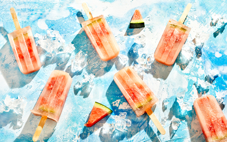 Scattered fresh healthy watermelon frozen ice popsicles on a blue background with crushed ice cubes in a flat lay still life from above