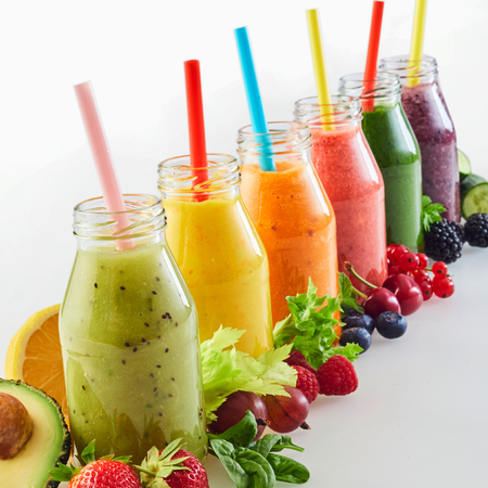 Bottles of assorted healthy fresh vegetable and fruit smoothies in a receding diagonal row with straws and copy space surrounded by the tropical ingredients in square format
