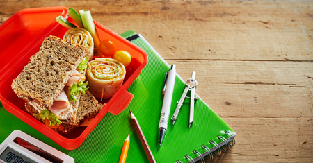 Healthy school lunch box with nutritious food including a wholegrain ham and lettuce sandwich, diced fresh vegetables and two small Rolex Rolls on chappati high angle on a notebook on a wooden desk